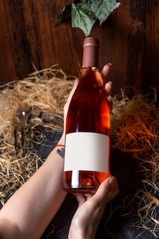 Eine vorderansichtfrau, die weinflasche des weißweins auf dem braunen hintergrundalkoholtrink-weingut hält