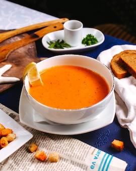 Eine vordere ansicht merji suppe ostgericht orange, die zusammen mit zitrone auf dem blauen boden serviert wird