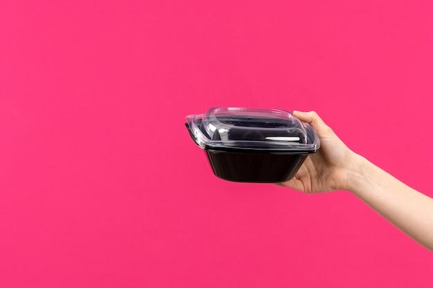 Eine vordere ansicht schwarze schüssel hand hält schwarze schüssel weibliche hand rosa hintergrundfarbe besteck küche