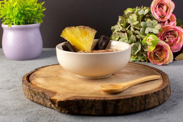 Eine vordere geschlossene ansicht choco dessert braun mit ananasscheibe choco bars blumen auf dem braunen holzschreibtisch und grau