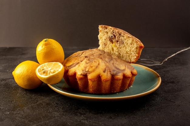 Eine vordere geschlossene ansicht runder süßer kuchen köstlicher leckerer schoko-kuchen, der in blauen teller zusammen mit frischen zitronen im dunkeln geschnitten wird