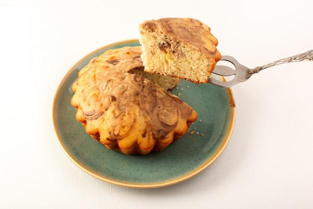 Eine vordere geschlossene ansicht runder süßer kuchen köstlicher leckerer schokoladenkuchen, der innerhalb des blauen tellers auf dem weiß geschnitten wird
