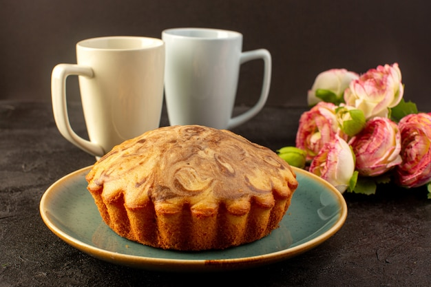Eine vordere geschlossene ansicht runder süßer kuchen köstlicher leckerer schokoladenkuchen innerhalb des blauen tellers zusammen mit zwei weißen tassen auf der dunkelheit