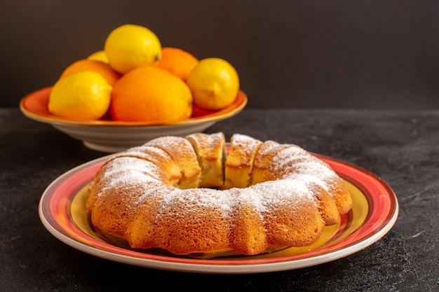 Eine vordere geschlossene ansicht süßer runder kuchen mit zuckerpulver geschnitten süßer köstlicher isolierter kuchen innerhalb platte zusammen mit zitronen und grauem hintergrundkekszuckerplätzchen