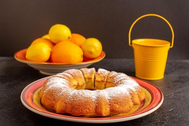 Eine vordere geschlossene ansicht süßer runder kuchen mit zuckerpulver geschnitten süßer köstlicher isolierter kuchen innerhalb platte zusammen mit zitronen
