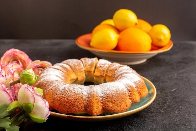 Eine vordere geschlossene ansicht süßer runder kuchen mit zuckerpulver oben zusammen mit zitronen geschnittenen süßen köstlichen isolierten innenplatte