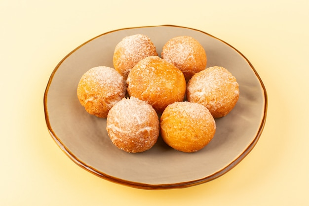 Eine vordere geschlossene ansicht zuckerpulverkuchen um süße gebackene köstliche kleine kuchen innerhalb der runden plattform