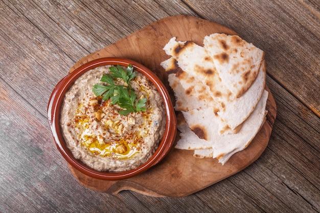 Eine vorspeise esme, baba ganush der levantinischen küche aus gebackenen auberginen und sesampaste, püriert mit olivenöl und gewürzen, kräutern und walnüssen mit lavash-stücken auf einem holzbrett. von oben betrachten