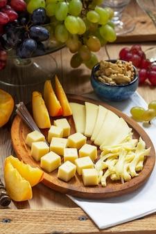 Eine vorspeise mit verschiedenen käsesorten, trauben und walnüssen, serviert mit wein. rustikaler stil.
