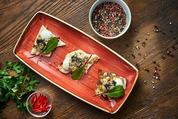 Eine vorspeise vor dem hauptgericht - rindersteak-tartar, serviert auf croutons in einem roten teller auf einem holztisch. restaurant essen.