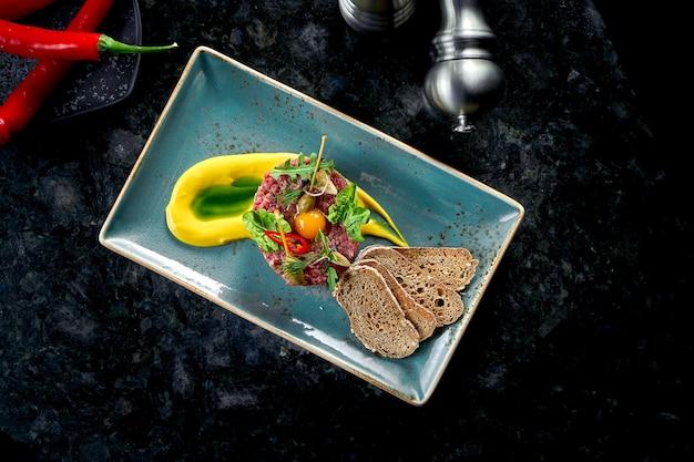 Eine vorspeise vor dem hauptgericht - rindersteak-tartar, serviert mit croutons, cappers, eigelb, gurken in einem blauen teller auf einem marmortisch. restaurant essen. rohes fleisch