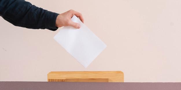 Eine wählerhand legte papier in die urne, demokratiewahl