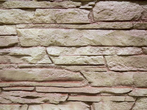 Eine wand aus einer künstlichen grauen steinfassade mit rauen bruchflächen