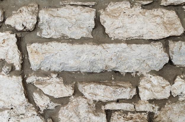 Eine wand aus natursteintravertin. travertin - naturstein aus der einrichtung und verkleidung von fassaden von gebäuden und innenräumen