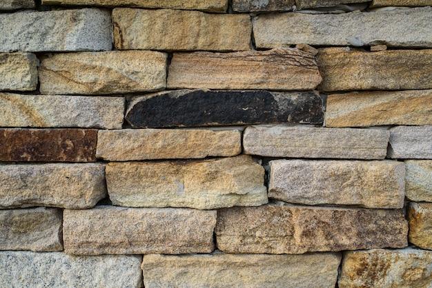 Eine wand aus schönem stein auf der straße. hintergrund. textur.