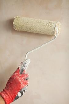 Eine wand in weiß streichen. ein rollenarm