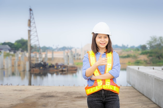 Eine weibliche architektin, die am brückenbau steht, einen schutzhelm trägt und die blaupause des projekts hält holding