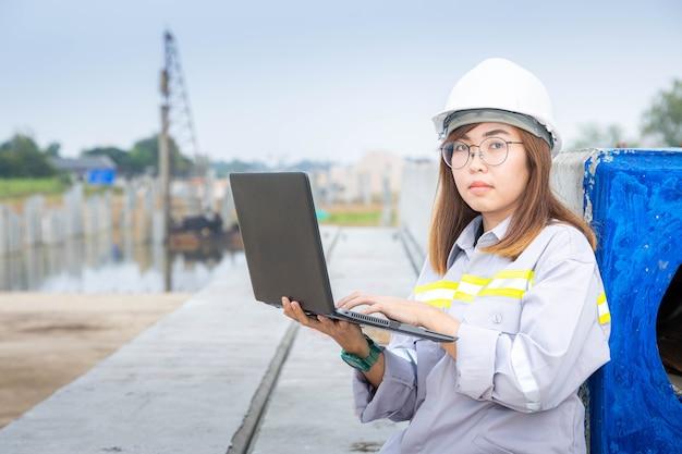 Eine weibliche architektin, die mit laptop auf der baustelle oder auf der baustelle arbeitet working