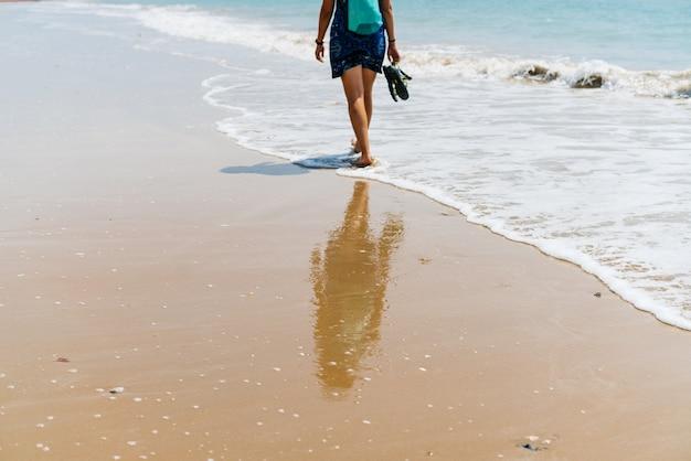 Eine weibliche figur geht entlang der linie des ozeans entlang des sandes