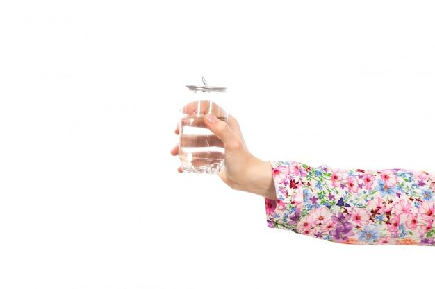 Eine weibliche hand der vorderansicht, die glas wasser auf dem weiß hält