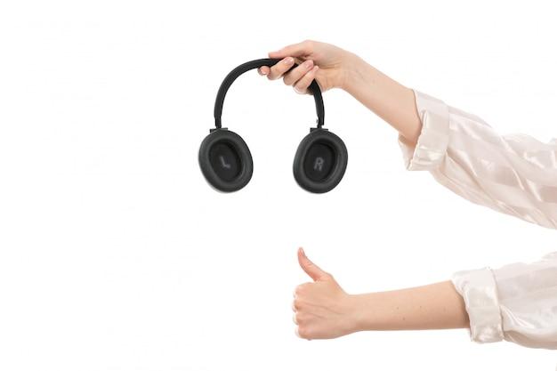 Eine weibliche hand der vorderansicht, die schwarze kopfhörer auf dem weiß hält