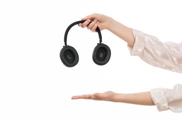 Eine weibliche hand der vorderansicht, die schwarze kopfhörer hält, die leere handfläche auf dem weiß zeigen