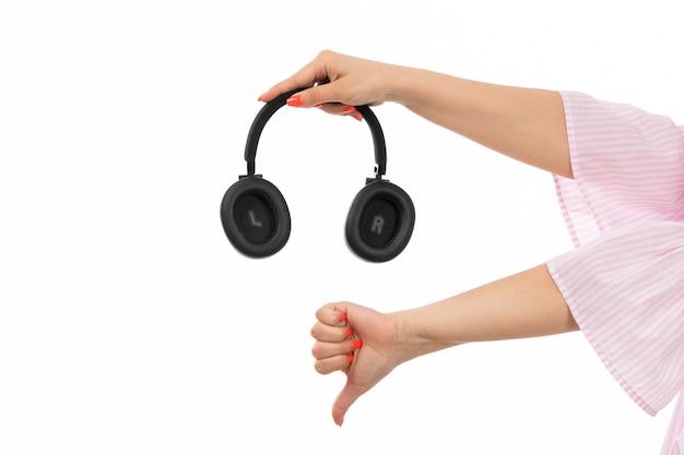 Eine weibliche hand der vorderansicht, die schwarze kopfhörer hält, die unähnliches zeichen auf dem weiß zeigen