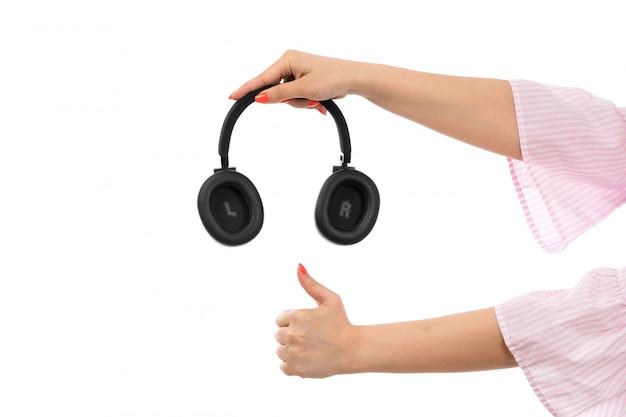 Eine weibliche hand der vorderansicht, die schwarze kopfhörer wie zeichen auf dem weiß hält
