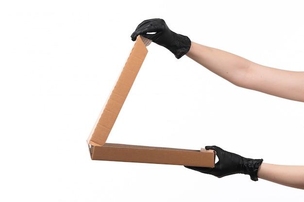 Eine weibliche hand der vorderansicht in den schwarzen handschuhen, die eine leere pizzaschachtel auf weiß halten