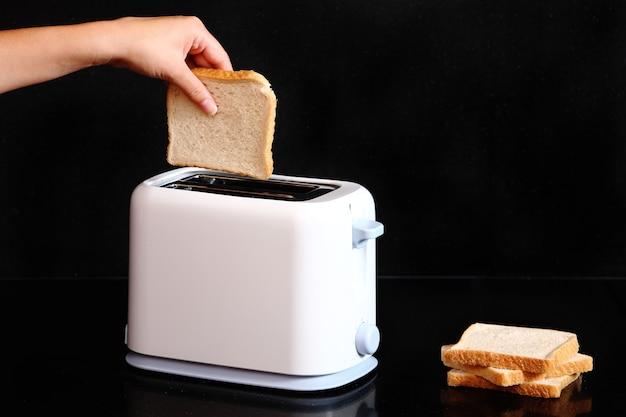 Eine weibliche hand, die ein stück toast auf einen toaster auf schwarzem hintergrund legt