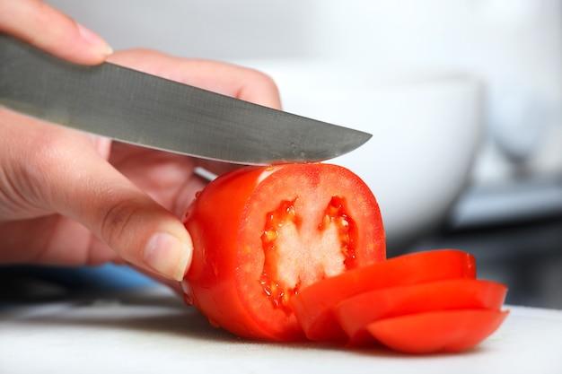Eine weibliche hand, die in der küche eine tomate schneidet