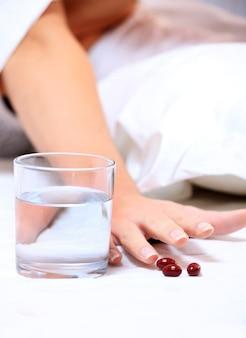 Eine weibliche hand, die nach einigen tabletten auf weißem hintergrund greift