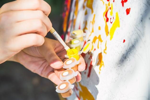 Eine weibliche hand dunks einen pinsel in gelber farbe, um auf der leinwand mit zahlen zu zeichnen