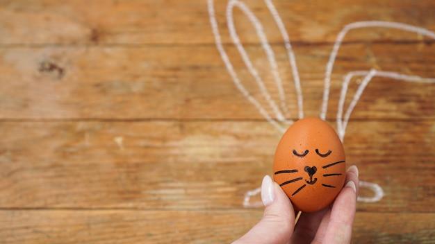 Eine weibliche hand hält ein ei mit einem niedlichen gesicht. die ohren sind mit kreide auf eine holzoberfläche gezeichnet. osterkonzept. feiertagspostkarte