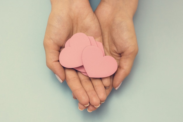 Eine weibliche hand hält ein hölzernes herz, das konzept der liebe