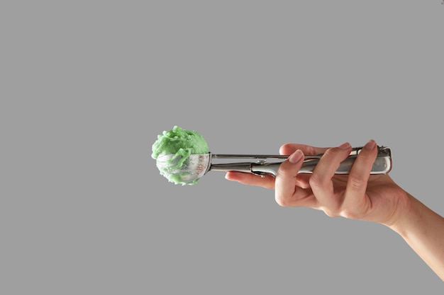 Eine weibliche hand hält eine metallschaufel mit grünem fruchteis an einer grauen wand mit platz für text. kaltes sommerdessert. Premium Fotos
