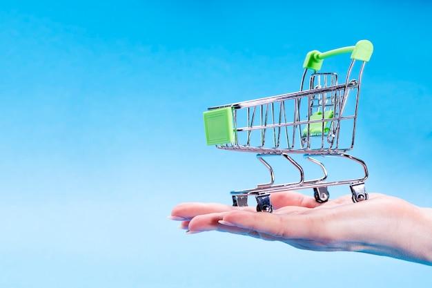 Eine weibliche hand hält einen leeren einkaufswagen auf einem blau in der hand.