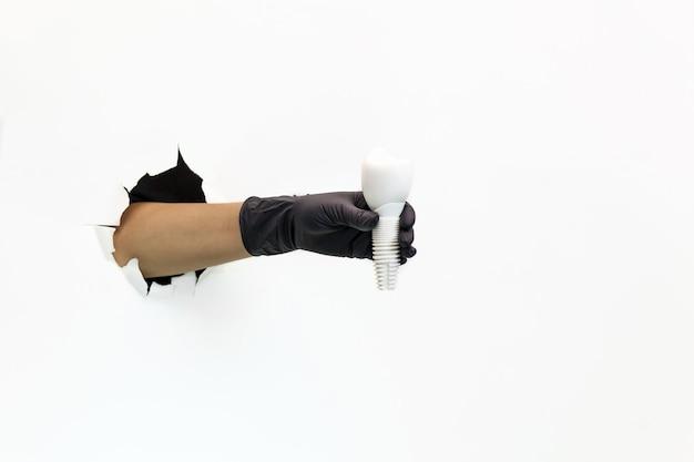 Eine weibliche hand in einem schwarzen gummihandschuh durch zerrissenes weißes papier hält ein weißes plastikmodell