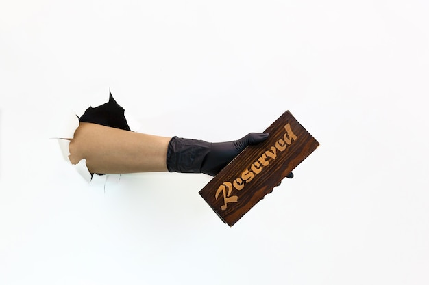 Eine weibliche hand in einem schwarzen latexhandschuh durch zerrissenes papier auf weißem hintergrund hält eine holzplatte zum reservieren. quarantänemaßnahmen zur verhinderung der verbreitung von covid 19. behandschuhte hand durch zerrissenes papier.