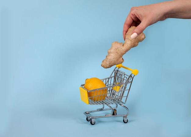 Eine weibliche hand legt ingwer in einen supermarktwagen