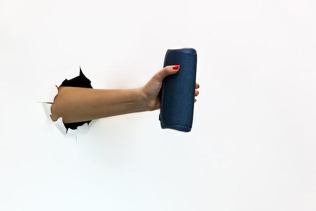 Eine weibliche hand mit einem roten nagellack durch zerrissenes weißes papier hält einen drahtlosen tragbaren lautsprecher. hand durch zerrissenes weißes papier