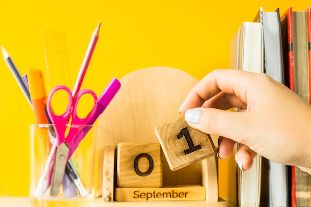 Eine weibliche hand setzt einen würfel mit dem datum vom 1. september auf einen hölzernen kalender