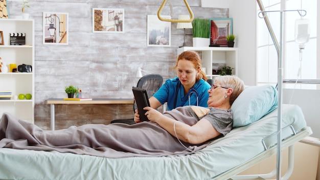 Eine weibliche pflegekraft hilft einer alten behinderten frau, die im krankenhausbett liegt, einen digitalen tablet-pc zu benutzen. helles zimmer mit großen fenstern