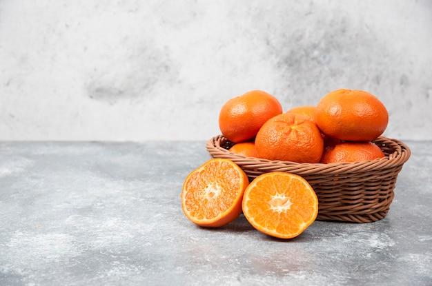 Eine weidenkiste voller saftiger orangenfrüchte auf steintisch.