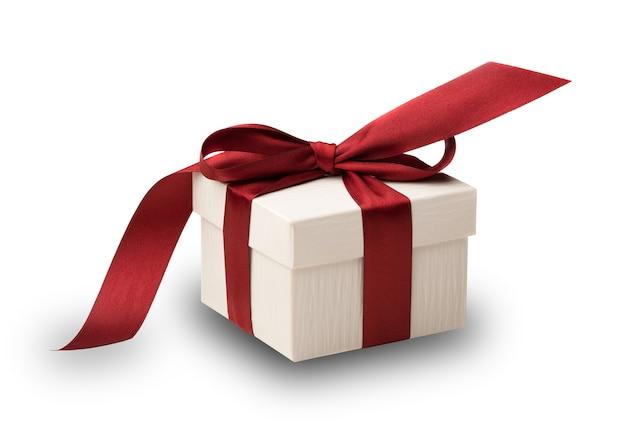 Eine weiße box, die mit einer roten schleife gebunden ist, die auf weiß mit beschneidungspfad isoliert ist?