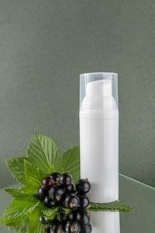 Eine weiße flasche mit kosmetikprodukt und zweig schwarzer johannisbeere auf spiegel, grüner hintergrund. natürliches organisches schönheitskosmetikkonzept. vorderansicht.