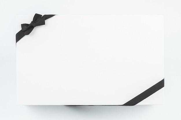 Eine weiße geschenkbox verziert mit einem schwarzen band