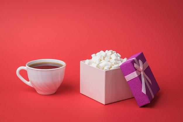 Eine weiße kaffeetasse und eine marshmallow-geschenkbox. ein süßer genuss.