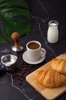 Eine weiße kaffeetasse wurde neben eine milchflasche und ein croissant auf ein schneidebrett gestellt, kaffeebohnen und mühlen auf einen marmorboden.