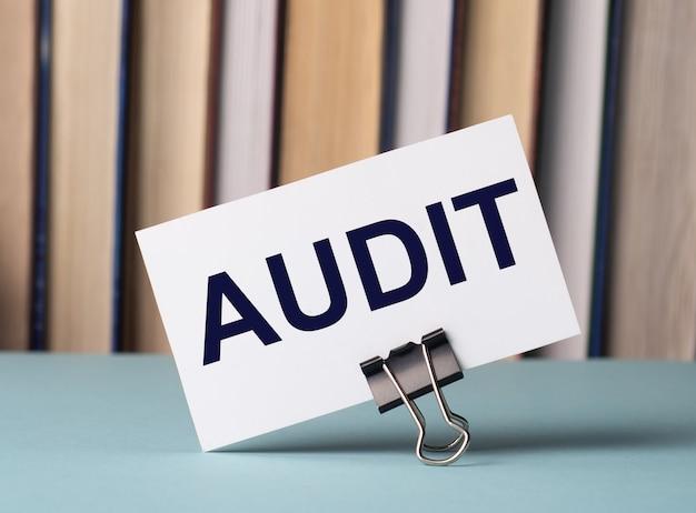 Eine weiße karte mit dem text audit steht auf einem clip für papiere auf dem tisch vor dem hintergrund von büchern. defokussieren